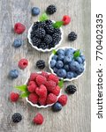 sweet berries mix on wooden... | Shutterstock . vector #770402335