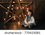 little pretty girl sits on the... | Shutterstock . vector #770425081
