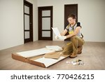 Small photo of Carpenter checking assemble paper manual. Assembly forniture instructions