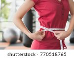 young slim woman measuring her... | Shutterstock . vector #770518765