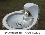 Small photo of Metal park drinking fountain with bowl on a concrete plinth with a pebble dashed exterior.