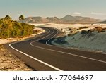 Winding road across the dunes of Corralejo, Fuerteventura, in the Canary Islands, Spain. - stock photo