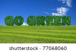 Textured go green sign over fresh grass and blue sky background. - stock photo