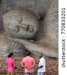 Small photo of POLONNARUWA, SRI LANKA - JANUARY 30, 2015: Local guide presenting famous Gal Vihara Buddha statue to a couple of tourists.