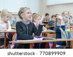 Small photo of Kharkov, Ukraine - November 30, 2017: Smiling children raise their hands sitting at a desk in an elementary school. Special school for a new program of study