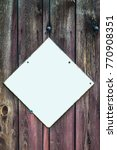 Small photo of Vintage blank white metal advertisement hoarding set in a diamond shape screwed to weathered wood background.
