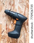 Small photo of Black handy cordless screwdriver machine isolated on abstract wooden wall.