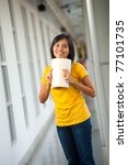 A cute young Asian student in yellow t-shirt, jeans holding, bending a textbook is smiling in a university campus hallway looking away from camera. 20s female Thai model of Chinese descent - stock photo