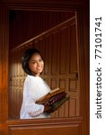 Lovely Thai girl wearing white blouse holding folded clothes looking away through window of a traditional teak wood house.  20-30 female Asian Thai model of Chinese descent - stock photo