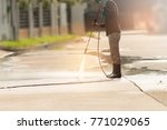 worker cleaning driveway with... | Shutterstock . vector #771029065