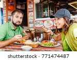 man and woman tourists eat in... | Shutterstock . vector #771474487