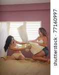 two caucasian female friends playing pillow fight in bedroom. Vertical shape, side view, full length, copy space - stock photo