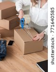 Small photo of partial view of entrepreneur packing customers parcel with adhesive tape