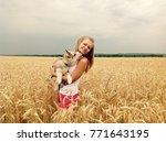 husky puppy licks a girl in her ... | Shutterstock . vector #771643195