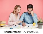 Small photo of Affectionale lovely female tries to help her husband, looks attentively what man writes, wants to give some advice how make financial report correctly and encourage him. People and team work concept