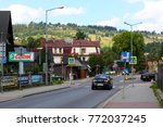 Small photo of Zakopane, Poland - August 15, 2017: A street view with little traffic, there are only a few cars and a few people. There are road signs and the hill in the distant is illuminated by sunlight.