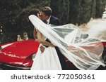 wind blows bride's veil while... | Shutterstock . vector #772050361