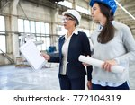 Small photo of Pretty middle-aged investor wearing classical suit and protective helmet walking along production department of modern plant and taking necessary notes, young engineer accompanying her