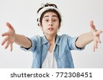 Small photo of Pretty girl with wide opened eyes wearing do-rag and denim shirt asking for something, stretching her arms to camera to get what she wants. Cute dark-haired young poses against white blank wall