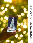 Small photo of blurred christmas tree replay on screen of smart phone with bokeh background