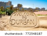 Welcome to Durban sand sculpture with skyline of Durban bay of plenty in the background