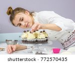 young woman decorates cupcakes | Shutterstock . vector #772570435