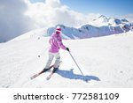 young woman skiing on a snowy... | Shutterstock . vector #772581109