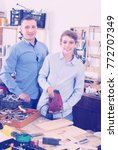 Small photo of Portrait of father and son cutting wooden plank with fret saw in workplace at garage