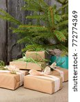 Small photo of Group of festive decorated christmas gift boxes under small simple christmas tree. Happy winder holiday theme. Traditional rustic Xmas decor