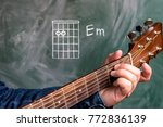 Small photo of Man in a blue denim shirt playing guitar chords displayed on a blackboard, Chord E minor