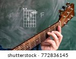 Small photo of Man in a blue denim shirt playing guitar chords displayed on a blackboard, Chord F