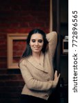 Small photo of Elegant Shy Woman in Warm Beige Wool Cardigan. Chic sophisticated fashion girl wearing a soft woolen sweater