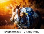 Stock photo beautiful asia girl taking care of her horse with love and caring 772897987
