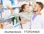 male pharmacist holding young... | Shutterstock . vector #772924465