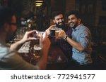 men drink beer in a pub. | Shutterstock . vector #772941577