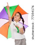 Little girl holding colored umbrella and pointing to sky - stock photo