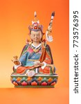 Small photo of The clay figurine of sitting Padmasambhava - Guru Rinpoche, make in a traditional Tibetan manner,  colorful painted, isolated on an orange background.