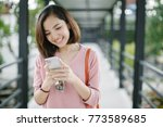 woman walking and using a smart ...   Shutterstock . vector #773589685