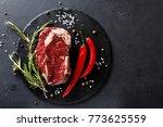 raw rib eye steak with herbs... | Shutterstock . vector #773625559