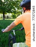 Small photo of a young man goes for a drive on a sporting bicycle on a background nature, sky, stone and afoot