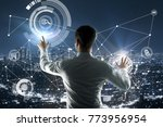 Small photo of Back view of young businessman pointing at abstract digital business hologram on city background. Infograph and finance concept. Double exposure
