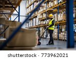 male warehouse worker pulling a ... | Shutterstock . vector #773962021