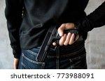 man hid gun behind their back ...   Shutterstock . vector #773988091
