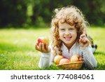 little girl is eating apple and ... | Shutterstock . vector #774084061