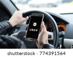JYVASKYLA, FINLAND - DECEMBER 7, 2017: Uber driver holding smartphone in car. Uber is an American company offering transportation services online. Illustrative editorial. - stock photo