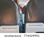 """Small photo of """" Lifejacket under your seat"""" and """"Fasten seatbelt while seated"""" the word on the airplane tray table at the seat back, black leather seat and the space between two seats."""
