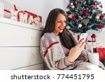 smiling young woman using phone ... | Shutterstock . vector #774451795