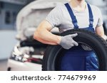 mechanic holding a tire tire at ... | Shutterstock . vector #774679969