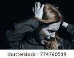 Small photo of Screaming woman with hallucinations and psychosis against black background