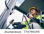 Small photo of Woman in reflective clothing operating heavy equipment